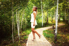 Όμορφο κορίτσι στο άσπρο φόρεμα στο πάρκο στοκ εικόνα με δικαίωμα ελεύθερης χρήσης