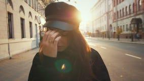Όμορφο κορίτσι στο αστικό τοπίο Όμορφο πρότυπο μόδας στη μαύρη ΚΑΠ φιλμ μικρού μήκους