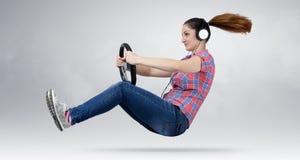 Όμορφο κορίτσι στο αυτοκίνητο οδηγών ακουστικών με μια ρόδα Στοκ Εικόνα