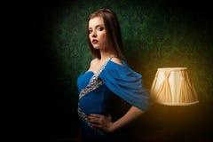 Όμορφο κορίτσι στο εκλεκτής ποιότητας δωμάτιο δίπλα στο λαμπτήρα Στοκ Εικόνα