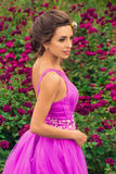 Όμορφο κορίτσι στο ιώδες φόρεμα μεταξύ στον κήπο Στοκ φωτογραφία με δικαίωμα ελεύθερης χρήσης