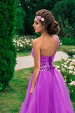 Όμορφο κορίτσι στο ιώδες φόρεμα μεταξύ στον κήπο Στοκ Φωτογραφία