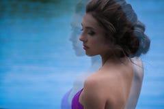 Όμορφο κορίτσι στο ιώδες φόρεμα μεταξύ στον κήπο Στοκ Φωτογραφίες