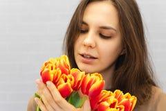 Όμορφο κορίτσι στο καφετί φόρεμα με τις τουλίπες λουλουδιών στα χέρια σε ένα ελαφρύ υπόβαθρο στοκ φωτογραφία
