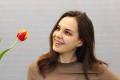 Όμορφο κορίτσι στο καφετί φόρεμα με τις τουλίπες λουλουδιών στα χέρια σε ένα ελαφρύ υπόβαθρο στοκ εικόνα με δικαίωμα ελεύθερης χρήσης