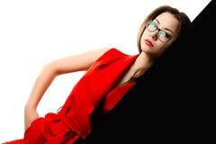 Όμορφο κορίτσι στο κόκκινο κοστούμι στο γραπτό υπόβαθρο Στοκ Εικόνες