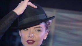 Όμορφο κορίτσι στο μαύρο τοπ χορό, παιχνίδι με το καπέλο στο νυχτερινό κέντρο διασκέδασης Χαμόγελο στη κάμερα απόθεμα βίντεο