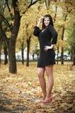 Όμορφο κορίτσι στο μαύρο φόρεμα στο κίτρινο πάρκο πόλεων, εποχή πτώσης Στοκ εικόνα με δικαίωμα ελεύθερης χρήσης