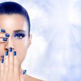 Όμορφο κορίτσι στο μπλε με τα χέρια στο πρόσωπό της Η τέχνη καρφιών και κάνει Στοκ Εικόνα