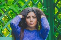 Όμορφο κορίτσι στο μπλε φόρεμα που θέτει τη συνεδρίαση στην κινηματογράφηση σε πρώτο πλάνο πάγκων Στοκ Φωτογραφίες