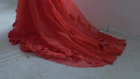 Όμορφο κορίτσι στο πανέμορφο κόκκινο φόρεμα με το hemline απόθεμα βίντεο