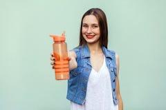 Όμορφο κορίτσι στο περιστασιακό ύφος με το πορτοκαλί μπουκάλι νερό στο πράσινο υπόβαθρο Στοκ Φωτογραφίες