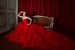 Όμορφο κορίτσι στο πολύ κόκκινο φόρεμα και στη βασιλική κορώνα στοκ φωτογραφίες