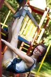 Όμορφο κορίτσι στο πλαίσιο αναρρίχησης στο πάρκο Στοκ Εικόνα
