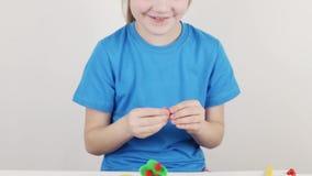 Όμορφο κορίτσι στο σπίτι μπλε φορμών από το plasticine στον άσπρο πίνακα απόθεμα βίντεο
