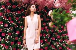 Όμορφο κορίτσι στο υπόβαθρο των λουλουδιών Στοκ Εικόνες