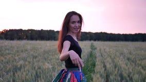 Όμορφο κορίτσι στο φόρεμα που περπατά μέσα μέσω του τομέα σχετικά με τα αυτιά σίτου στο ηλιοβασίλεμα φιλμ μικρού μήκους