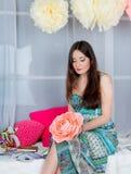 Όμορφο κορίτσι στο χρωματισμένο στούντιο ντεκόρ Εξέταση το λουλούδι Στοκ φωτογραφίες με δικαίωμα ελεύθερης χρήσης