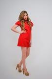 όμορφο κορίτσι φορεμάτων που θέτει το κόκκινο Στοκ Φωτογραφίες