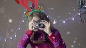 Όμορφο κορίτσι Χριστουγέννων με τα κέρατα ταράνδων, που χαμογελούν και που παίρνουν τις εικόνες με την αναδρομική κάμερα που απομ απόθεμα βίντεο