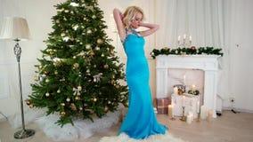 Όμορφο κορίτσι Χριστουγέννων που χορεύει σε ένα εορταστικό φόρεμα κοντά στο χριστουγεννιάτικο δέντρο στον εορτασμό Παραμονής Πρωτ απόθεμα βίντεο
