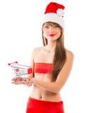 Όμορφο κορίτσι Χριστουγέννων Santa με το μικρό καροτσάκι αγορών στο wh Στοκ εικόνα με δικαίωμα ελεύθερης χρήσης