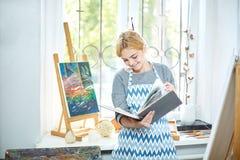 Όμορφο κορίτσι blode που κοιτάζει σε ένα λεύκωμα και ένα χαμόγελο Έννοια τέχνης, Στοκ εικόνα με δικαίωμα ελεύθερης χρήσης