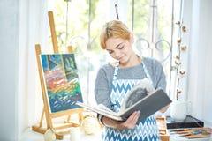 Όμορφο κορίτσι blode που κοιτάζει σε ένα λεύκωμα και ένα χαμόγελο Έννοια τέχνης, Στοκ Εικόνες