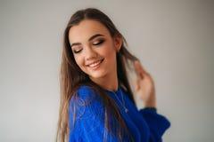 Όμορφο κορίτσι brunette με ένα καλό χαμόγελο σε μια μπλε τοποθέτηση μπλουζών για έναν φωτογράφο και την παρουσίαση makeup της στοκ εικόνες