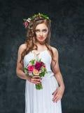 Όμορφο κορίτσι brunette με μια σύνθεση των λουλουδιών Στοκ Φωτογραφίες