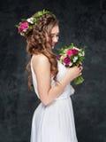 Όμορφο κορίτσι brunette με μια σύνθεση των λουλουδιών Στοκ Εικόνα