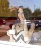 Όμορφο κορίτσι brunette με την προθήκη γυαλιού σε έναν καφέ, ηλιόλουστη ημέρα, που μιλά το τηλέφωνο Στοκ Εικόνες