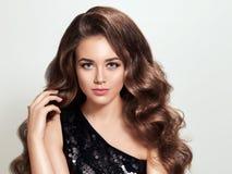 Όμορφο κορίτσι brunette με τη μακριά και λαμπρή σγουρή τρίχα όγκου Στοκ Εικόνες