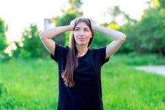 Όμορφο κορίτσι brunette με τη μακρυμάλλη και μαύρη μπλούζα Καλοκαίρι στη φύση μεταξύ των πράσινων λιβαδιών Κρατά το κεφάλι σε δικ στοκ εικόνα