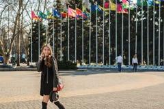 Όμορφο κορίτσι brunette με το έξυπνο τηλέφωνο στο walki περιστασιακών ενδυμάτων Στοκ Εικόνες