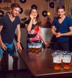 Όμορφο κορίτσι brunette που έχει τη διασκέδαση με τα δίδυμα που παίζει την μπύρα pong Στοκ Εικόνα