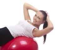 Όμορφο κορίτσι brunette που καθορίζει στο κόκκινο fitball Στοκ Εικόνα