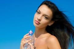Όμορφο κορίτσι brunette που κρατά ένα μπουκάλι νερό Στοκ εικόνα με δικαίωμα ελεύθερης χρήσης