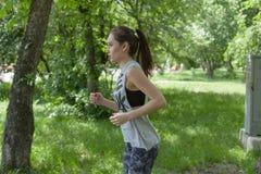 Όμορφο κορίτσι brunette που τρέχει στο πάρκο Στοκ Εικόνα