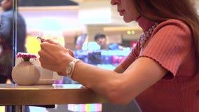 Όμορφο κορίτσι brunette που χρησιμοποιεί το κινητό τηλέφωνό της σε έναν καφέ Σύγχρονος κινητός τηλεφωνικός εθισμός 4k πυροβολισμό φιλμ μικρού μήκους