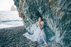 Όμορφο κορίτσι brunette σε ένα μακρύ γκρίζο φόρεμα με μια συνεδρίαση πέπλων θαλασσίως, κοντά στον απότομο βράχο, Στοκ εικόνες με δικαίωμα ελεύθερης χρήσης