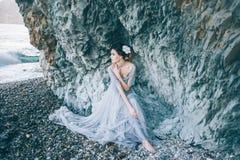 Όμορφο κορίτσι brunette σε ένα μακρύ γκρίζο φόρεμα με μια συνεδρίαση πέπλων θαλασσίως, κοντά στον απότομο βράχο, Στοκ Φωτογραφίες