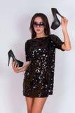 Όμορφο κορίτσι brunette σε ένα μαύρο φόρεμα και τα γυαλιά ηλίου, που κρατούν τα μαύρα ψηλοτάκουνα παπούτσια Στοκ Εικόνες