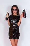 Όμορφο κορίτσι brunette σε ένα μαύρο φόρεμα και τα γυαλιά ηλίου, που κρατούν τα μαύρα ψηλοτάκουνα παπούτσια Στοκ εικόνες με δικαίωμα ελεύθερης χρήσης
