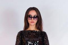 Όμορφο κορίτσι brunette σε ένα μαύρο φόρεμα και τα γυαλιά ηλίου Brunette με τη μακριά μαύρη τρίχα Στοκ Εικόνες