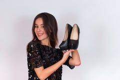 Όμορφο κορίτσι brunette σε ένα μαύρο φόρεμα που κρατά τα μαύρα ψηλοτάκουνα παπούτσια Στοκ φωτογραφίες με δικαίωμα ελεύθερης χρήσης