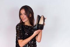 Όμορφο κορίτσι brunette σε ένα μαύρο φόρεμα που κρατά τα μαύρα ψηλοτάκουνα παπούτσια Στοκ Εικόνα