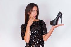 Όμορφο κορίτσι brunette σε ένα μαύρο φόρεμα που κρατά τα μαύρα ψηλοτάκουνα παπούτσια Στοκ Εικόνες
