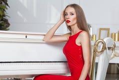 Όμορφο κορίτσι brunette σε ένα μοντέρνο φόρεμα βραδιού χειλικό κόκκινο όμορφες νεολαίες γυναικών στούντιο ζευγών χορεύοντας καλυμ Στοκ Εικόνα