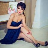 Όμορφο κορίτσι brunette σε μια μπλε συνεδρίαση φορεμάτων εκτός από τον καναπέ Στοκ Φωτογραφίες